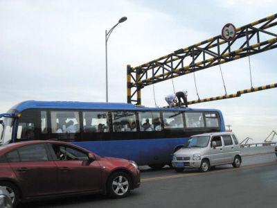 大客车被卡限高杆 两人爬上车顶抬杆通行