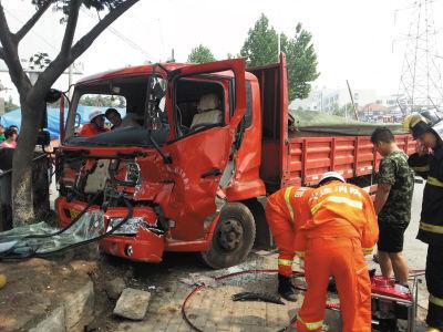 俩货车路口相撞一司机被卡车内