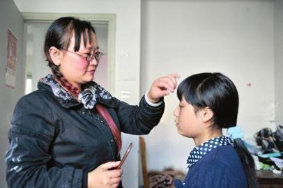 10月21日,在出租屋里,覃燕正在给女儿罗馨梳头。