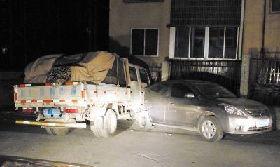 货车扎在护栏与路边停放的轿车车身上。